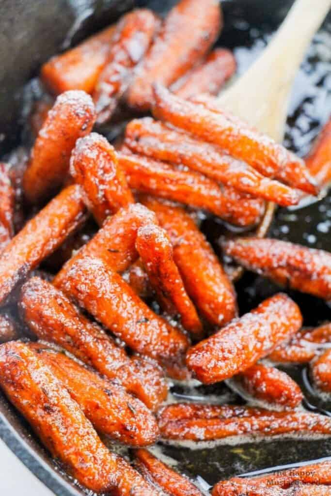 Candied carrot recipe in pan with wooden spoon