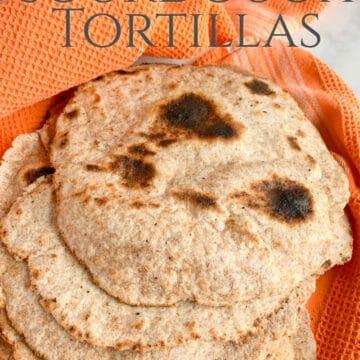 whole wheat sourdough tortillas wrapped in an orange kitchen towel to keep warm.