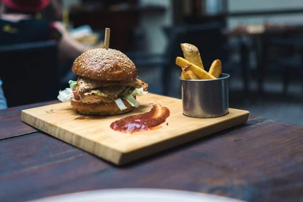 Burger and chips with sauce on a wooden tray