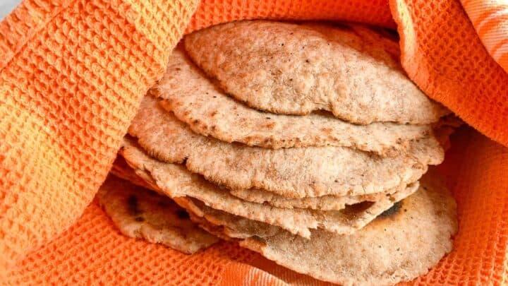 Whole Wheat Sourdough Tortillas wrapped in orange kitchen towel to keep warm.