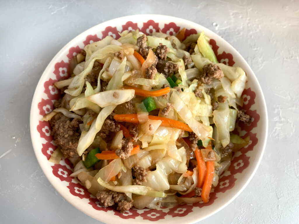 Top view of egg roll in a bowl in red and white bowl