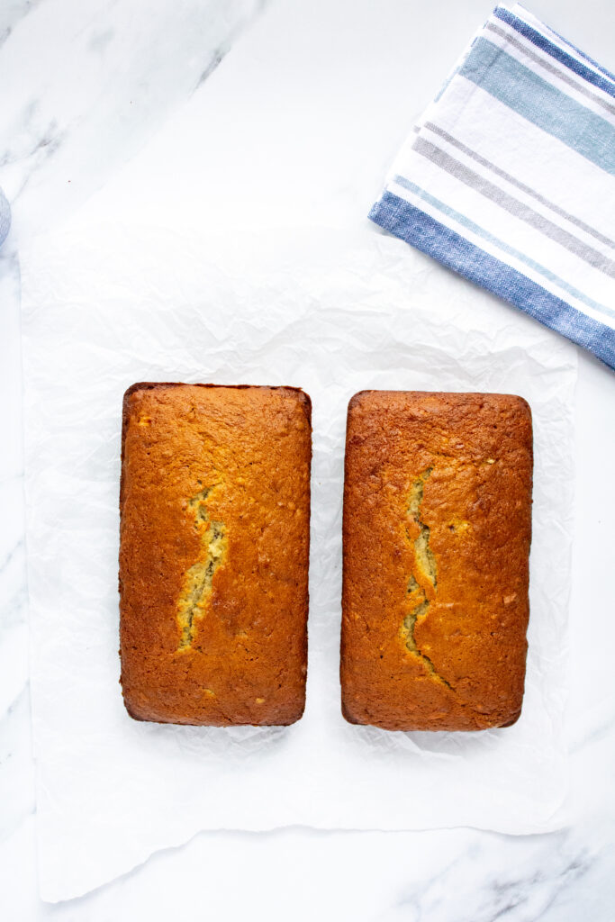 two loaves of banana bread on a white marble background