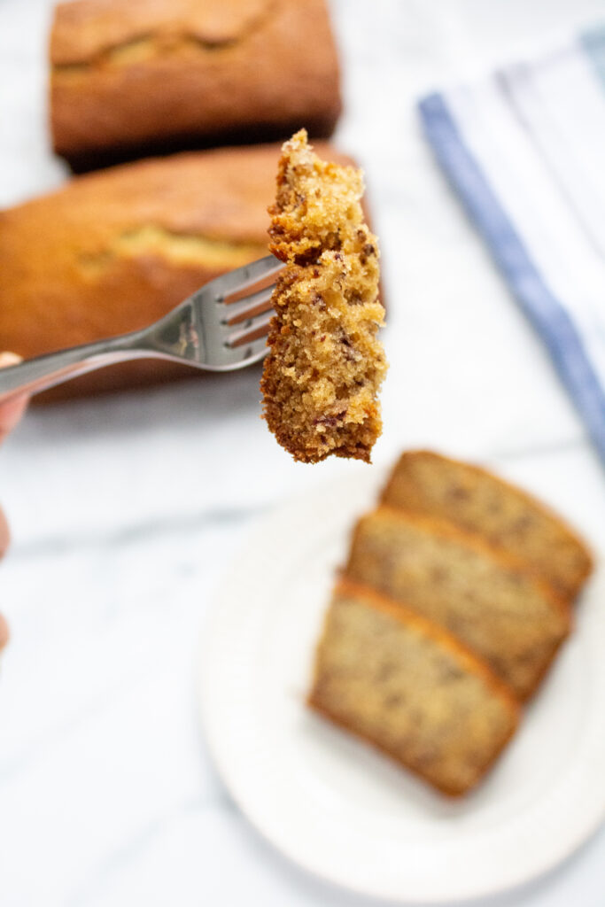 a fork holding a piece of banana bread