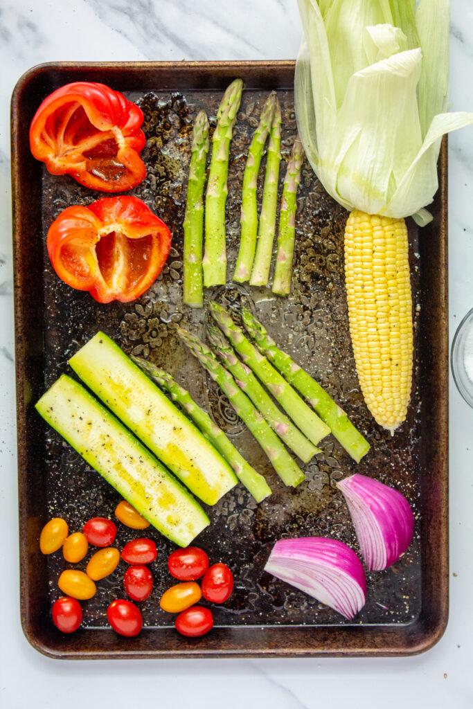 sliced and seasoned vegetables on baking sheet