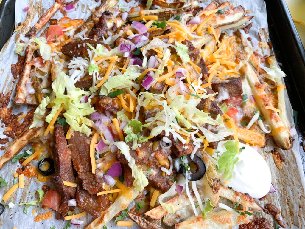 top view of carne asada fries with toppings such as steak, sour cream, lettuce, and olives with cheese