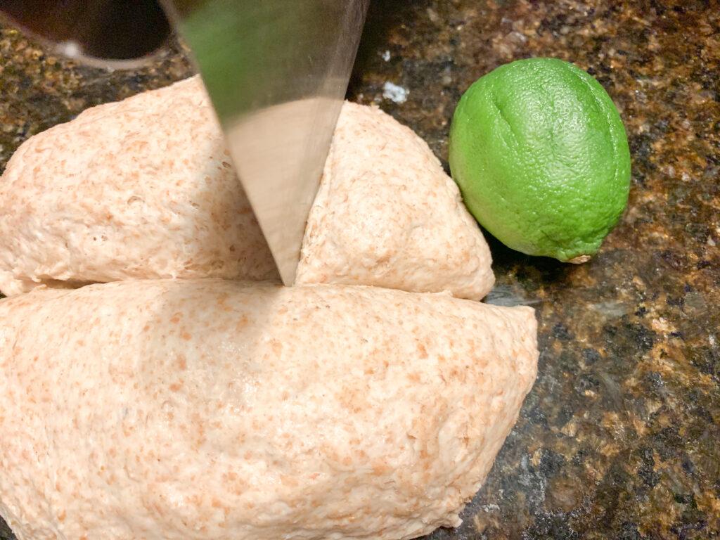 Sourdough discard pita bread recipe dough being cut with lime