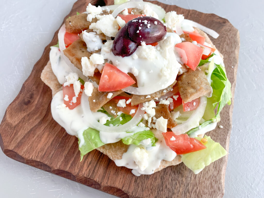 Pita bread using sourdough discard with veggies, cream, and cheese on wooden board