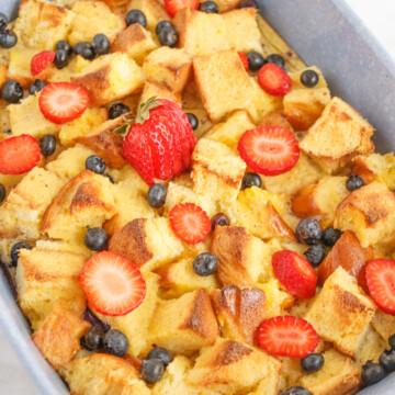 breakfast brioche casserole in dish with fresh blueberries and strawberries