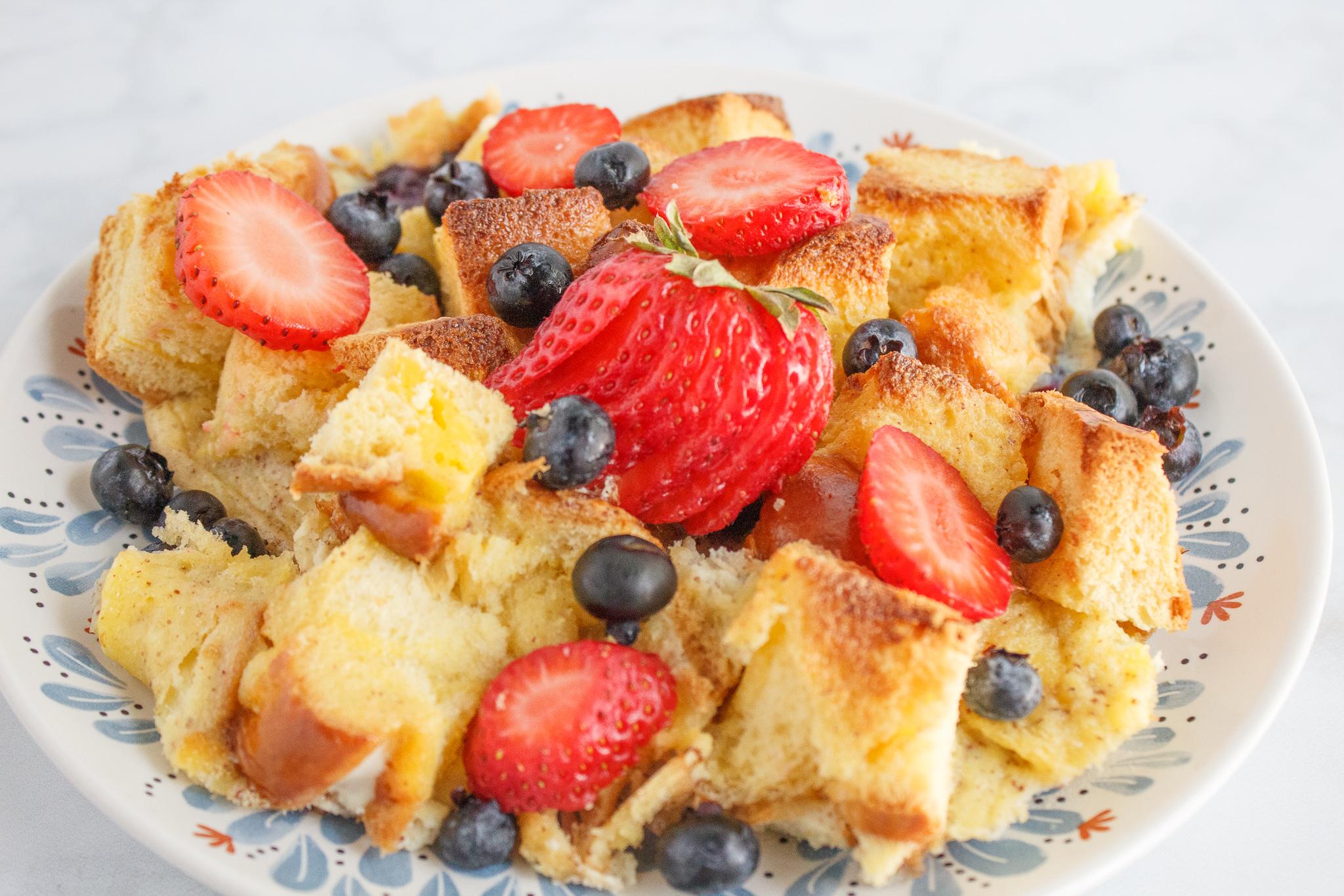 breakfast brioche casserole on a plate with fresh berries