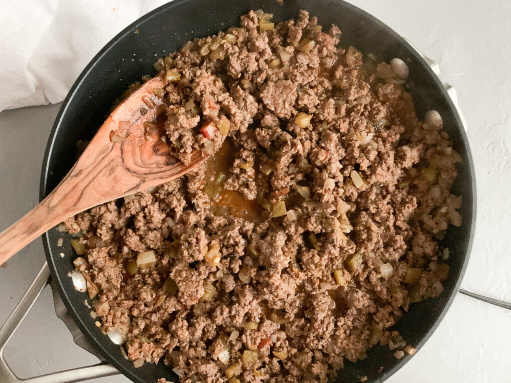 double decker taco ingredients in skillet with wooden spoon