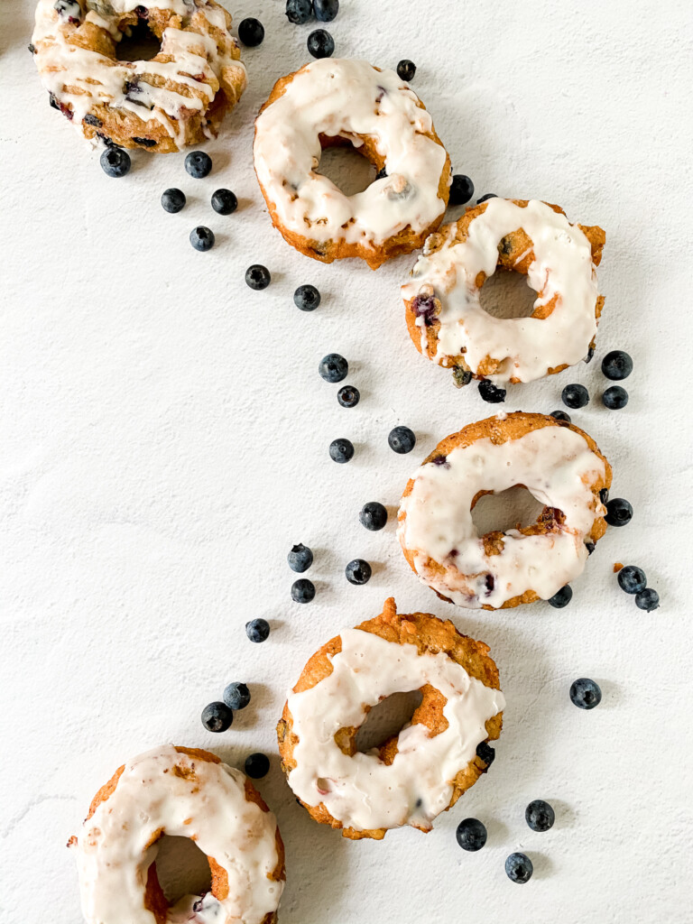 top view of raised sourdough donuts with glaze and blueberries