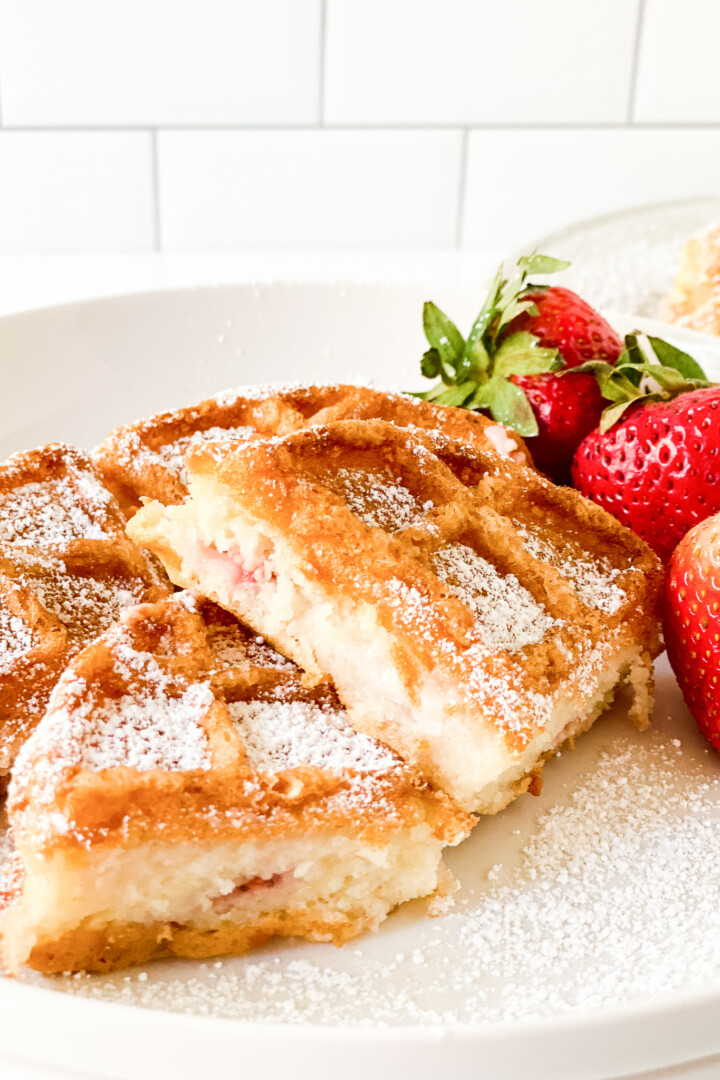 front view of sourdough waffle on white plate with strawberries