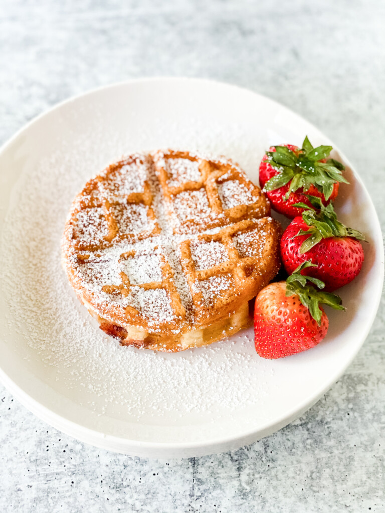 one Belgian waffle with powdered sugar and three strawberries on one white plate