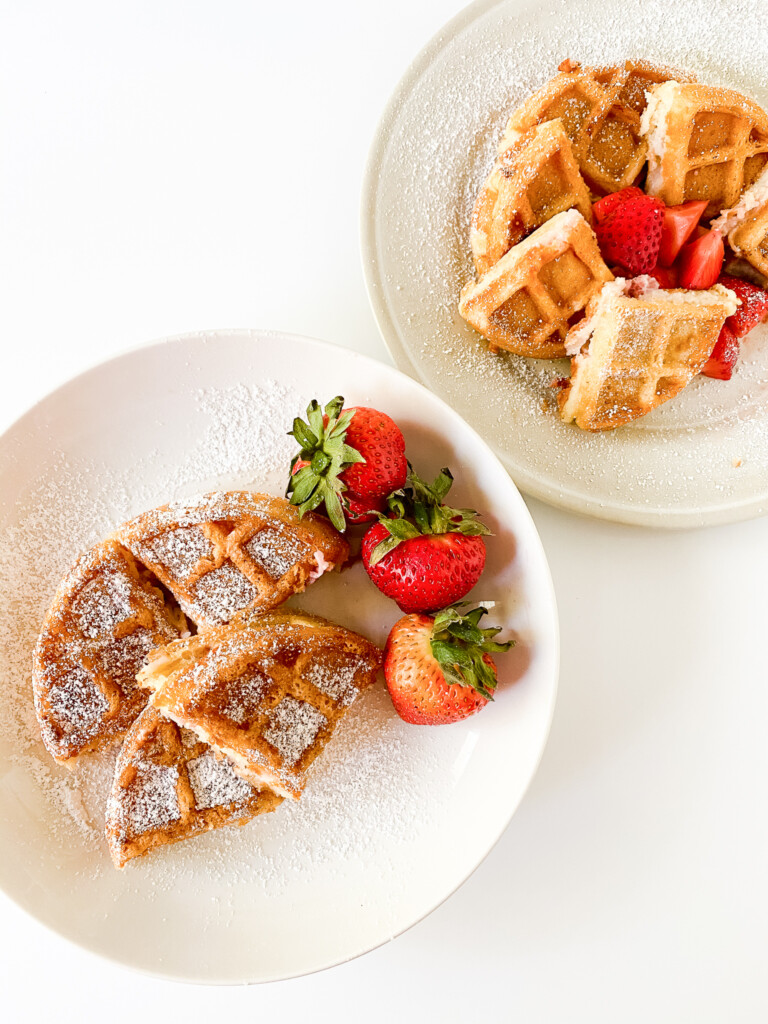 top view of sourdough waffles on white plate with strawberries and powdered sugar