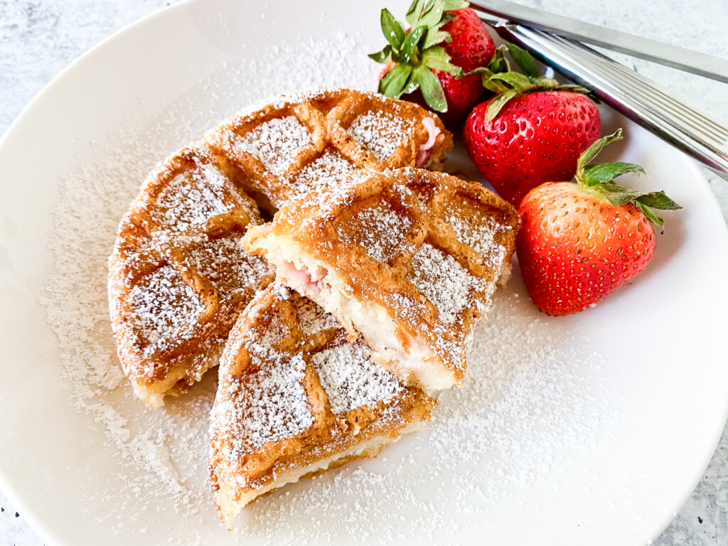 one waffle on white plate with three strawberries