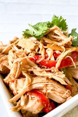 Crockpot chicken fajitas in white bowl with cilantro
