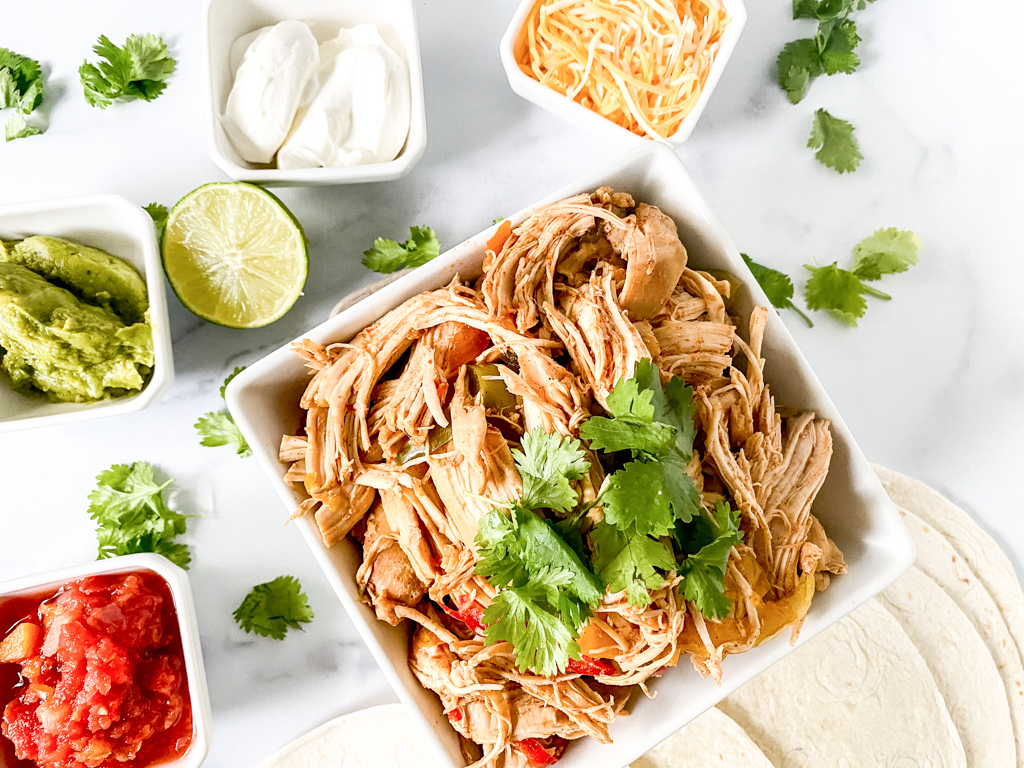 Crockpot-Chicken-Fajita-Ingredients such as lime, cilantro, cheese, sour cream, etc.