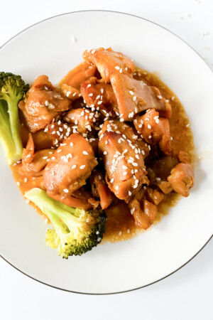crockpot sesame chicken on white plate with broccoli and sesame seeds