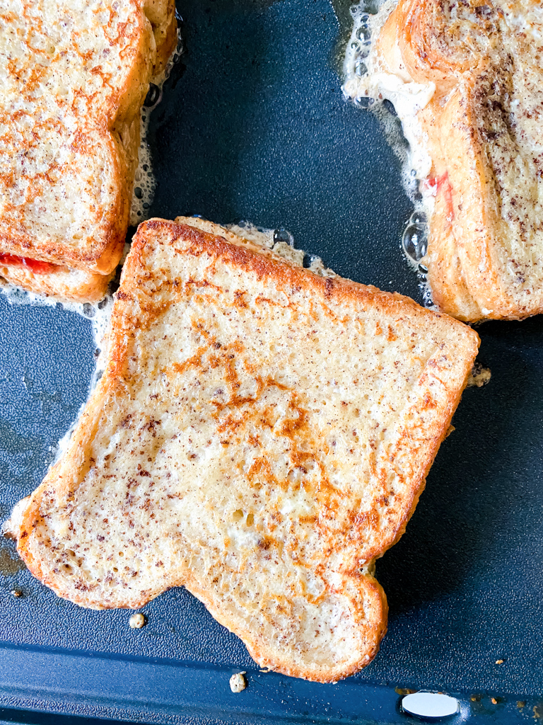 French-toast-peanut-butter-and-jelly-sandwich cooking on griddle with butter