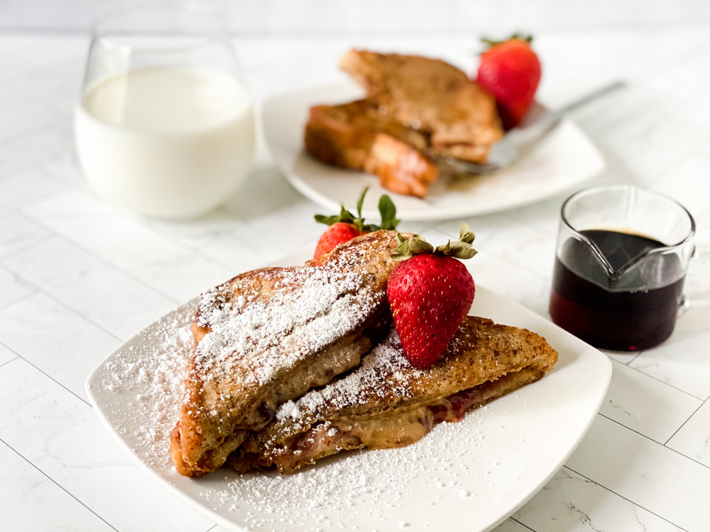 Double-Dip-French-Toast-Recipe with powdered sugar , syrup, and strawberries