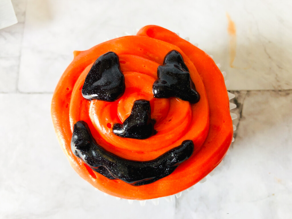 top view of orange cupcake with halloween face with black frosting