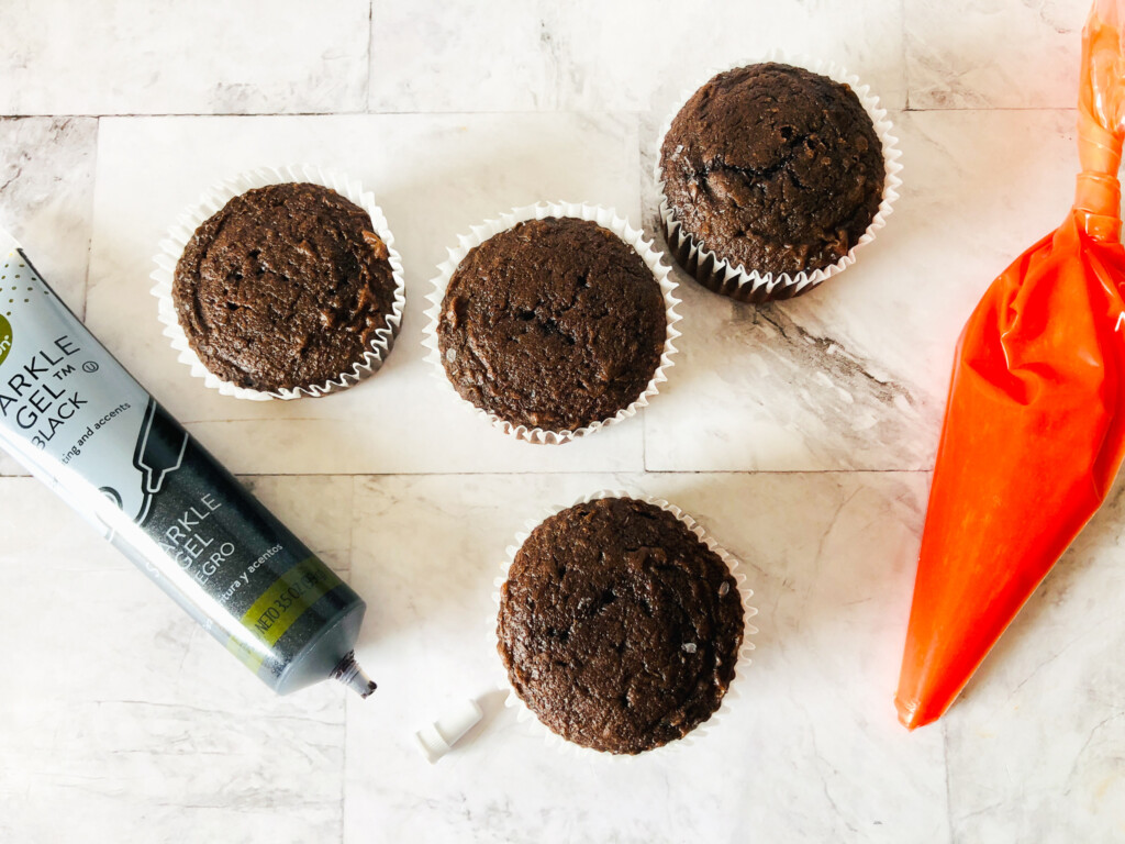 baked chocolate cupcakes with orange and black frosting
