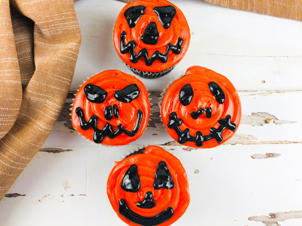 top view of jack o lantern cupcakes with black and orange frosting