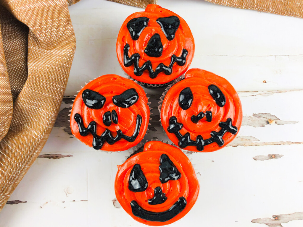 four halloween pumpkin cupcakes with orange and black frosting