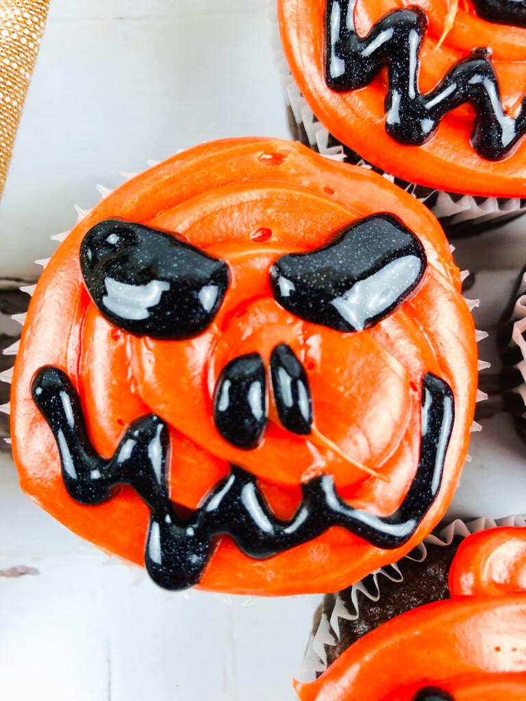 scary jack o lantern face on orange pumpkin cupcake